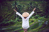 Asian Female with Traditional Straw and Raised Hands, praying at Rice Fields