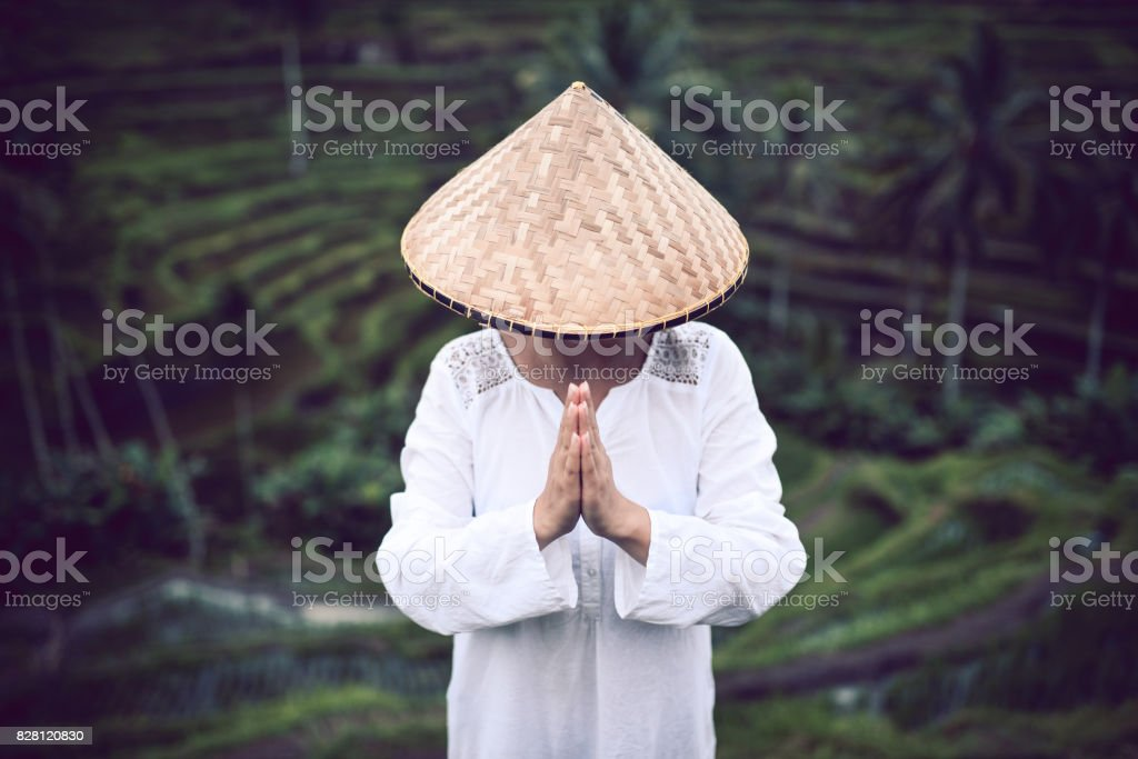 Asian Female with Traditional Straw how Praying at Rice Fields stock photo