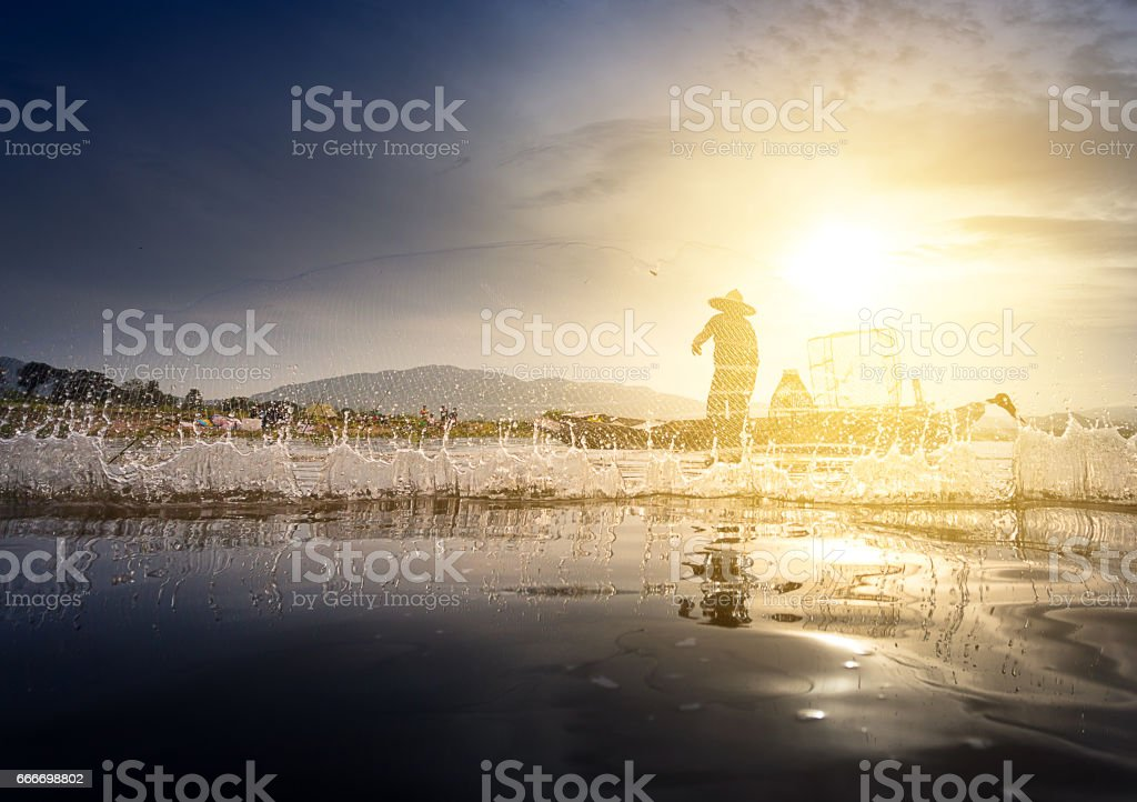 asian fisherman casting a net for catch a fish stock photo