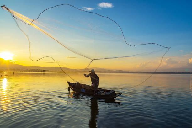 日の出前に早朝自然川の淡水魚をキャッチするための投網の木造船でアジアの漁師 - 漁師 ストックフォトと画像