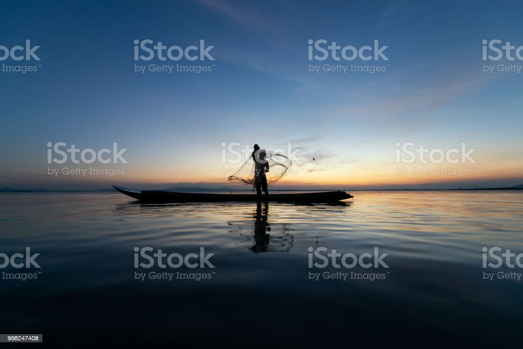 Asian fishermen on wooden boat for catching freshwater fish in nature river at before sunset is a culture of Thai. Concept way of life folk stock photo