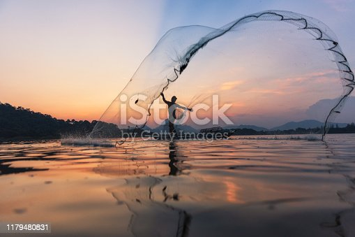 istock Asian fishermen throwing fishing net during twilight on wooden boat at the lake. Concept Fisherman's Lifestyle in countryside. Lopburi, Thailand, Asia 1179480831
