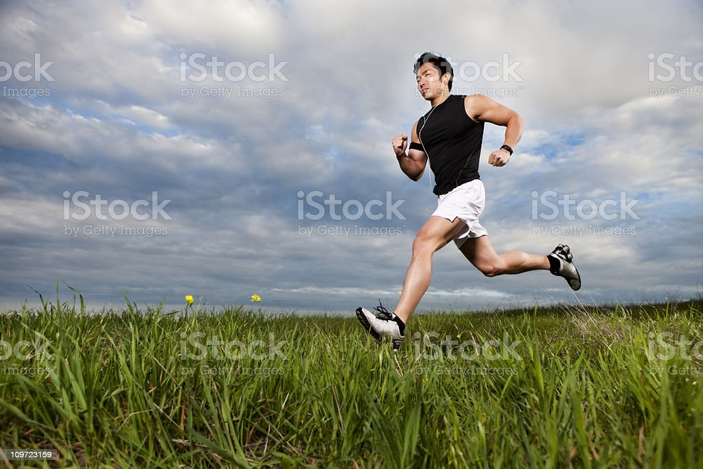 Asian Fitness Man Running Through Field royalty-free stock photo