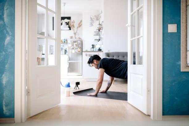 asiatische fitness vlogger kniet in seiza-position und trinken protein shake - promi zuhause stock-fotos und bilder