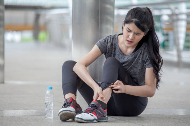 asian fitness young woman  Running injury leg accident  of workout exercising on street in urban city . sport runner girl sitting on floor sprained ankle in pain stock photo