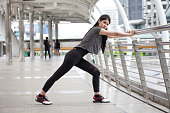 asian fitness young woman stretching leg on a rail bridge workout exercising on street in urban city . runner sport girl warm up . female athlete cool down