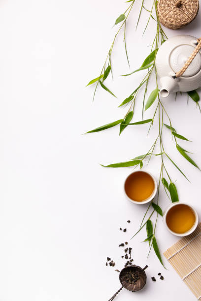 Asian food background set with green tea, cups and teapot with bamboo branches stock photo
