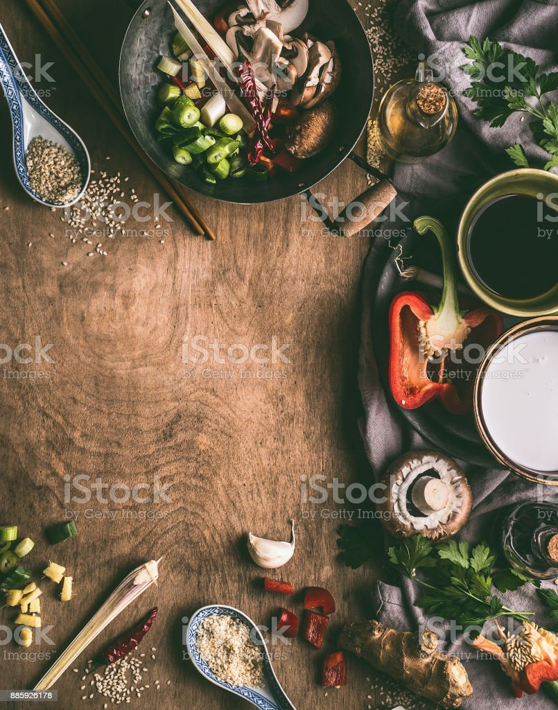 Asian food background with wok , coconut milk, soy sauce, sesame oil, chopped spices and vegetables stock photo