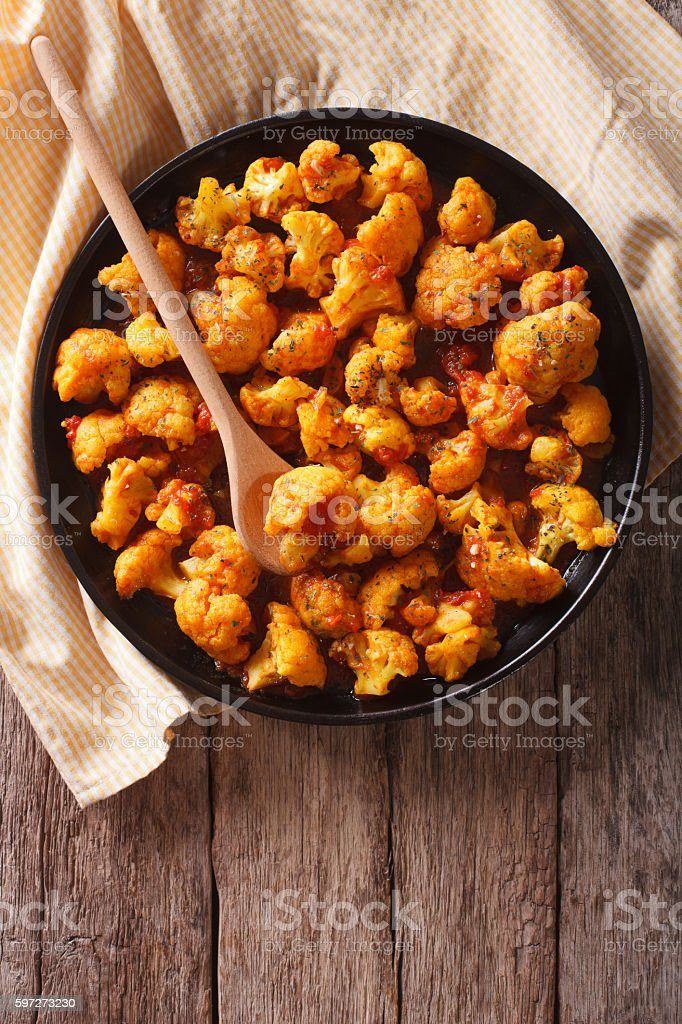 Asian food: cauliflower with tomatoes in curry. vertical top view Lizenzfreies stock-foto