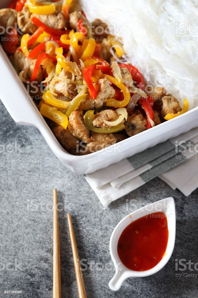 Asian food: fried chicken with tricolor bell peppers and rice vermicelli stock photo