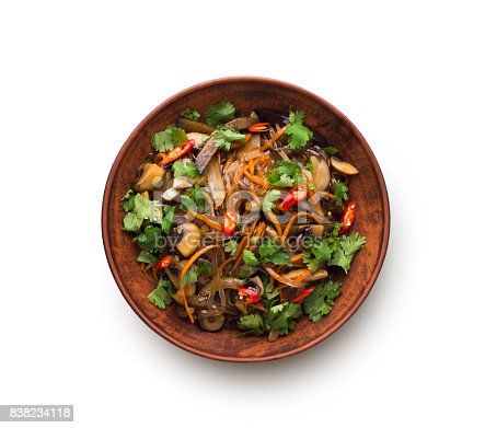 Asian restaurant healthy food delivery. Funchoza with meat and vegetables, soy sauce, chilli pepper and cilantro in a bowl isolated on white background, top view