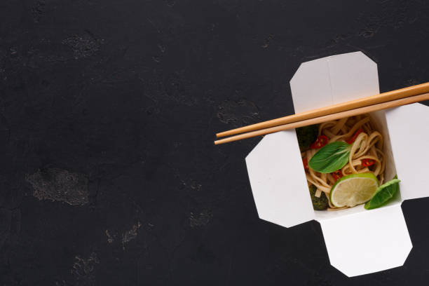 Asian food in delivery box on gray background Asian restaurant food delivery. Vegetarian stir fry with noodles, broccoli and green spinach on black background, top view, copy space chinese takeout stock pictures, royalty-free photos & images