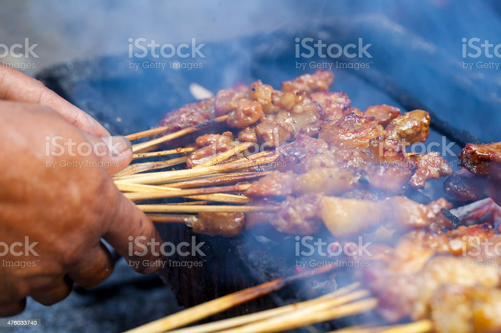 Asian food man cooking preparing satay outdoor stock photo