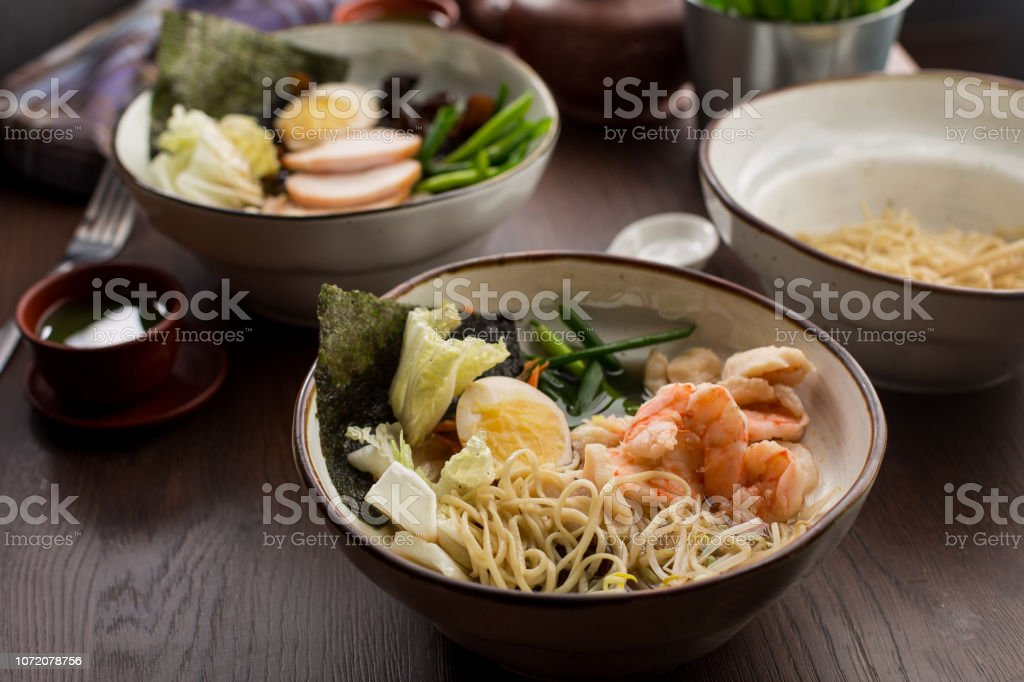 Asian food: ramen with chicken and shrimp on the table stock photo