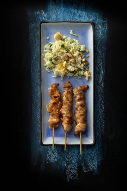 asiatische küche: yakitori und fried rice stillleben - hausgemachter gebratener reis stock-fotos und bilder
