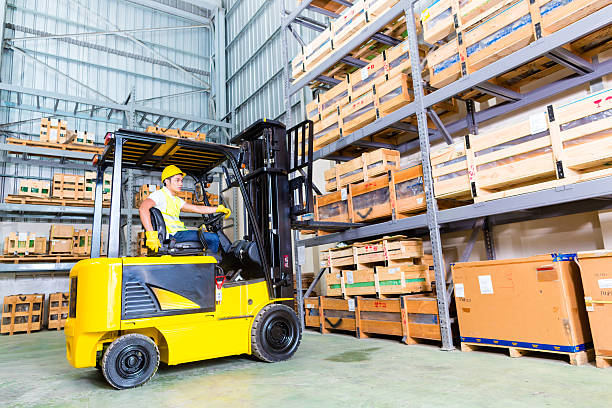 Asian fork lift truck driver lifting pallet in storage stock photo