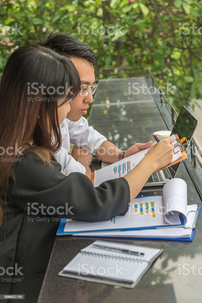 Asian freelancers having discussion about their project at cafeteria stock photo