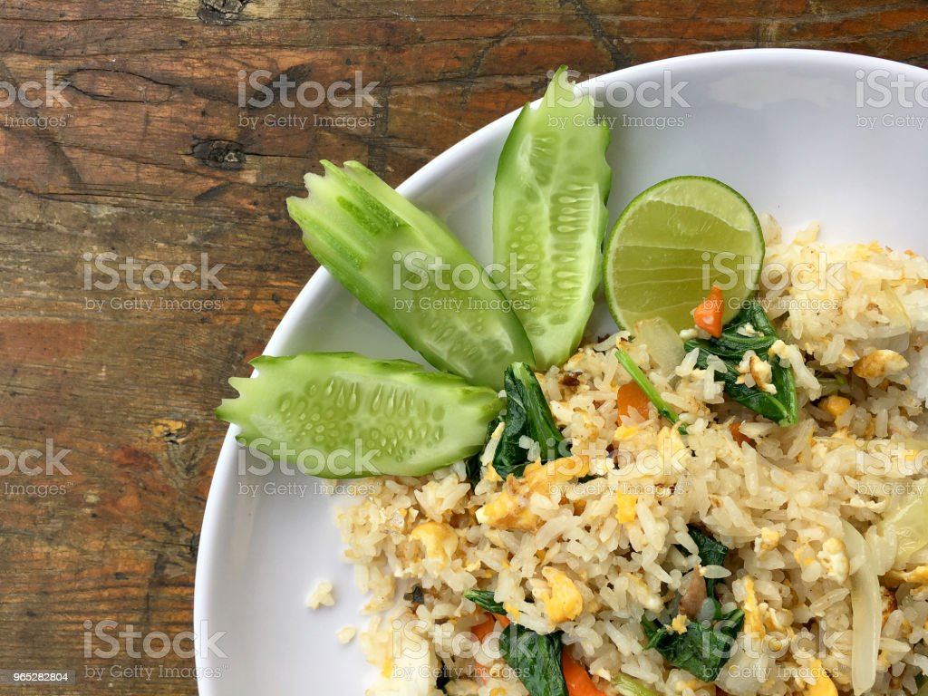 Asian fried rice with mackerel; egg and vegetable in white dish serve with slide cucumber on wooden background. Thai style food. zbiór zdjęć royalty-free