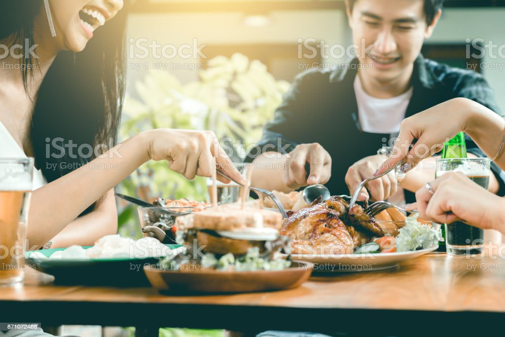 Asian friends enjoying eating turkey at restaurant. stock photo