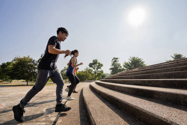 Asian friends group jogging up the stairs stock photo