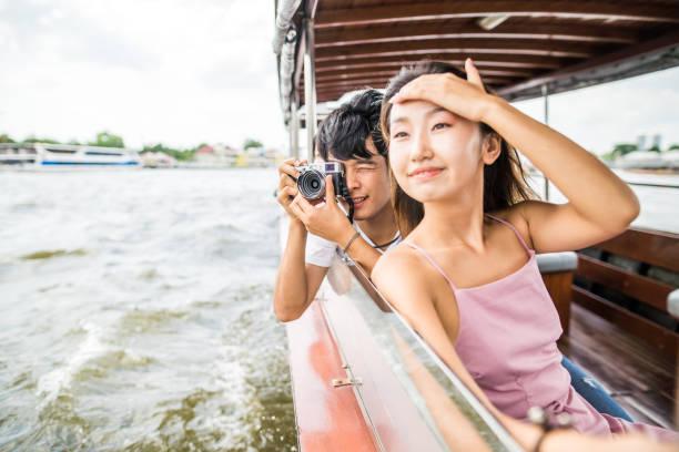 aziatische vrienden op de riviertour in bangkok naast wat arun - rondvaartboot stockfoto's en -beelden