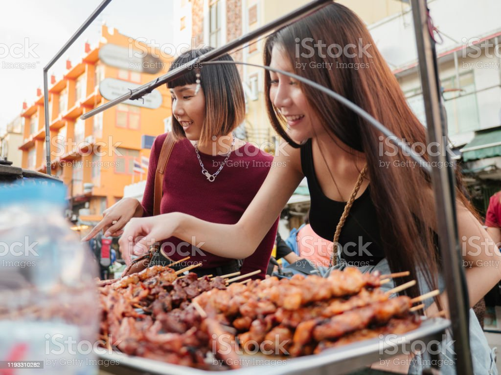 Asian Friends Tourists Choosing Bbq With Her Friend At The Flea Images, Photos, Reviews