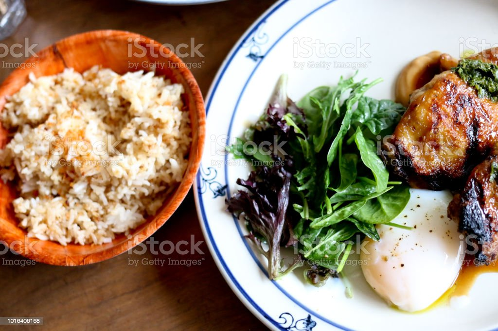 Asian fusion brunch with chicken adobo, fried garlic rice, poached egg and a spinach salad stock photo
