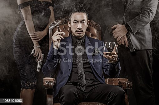 Handsome Asian Gangster Mafia Boss Man with security bodyguards in smoky studio shoot