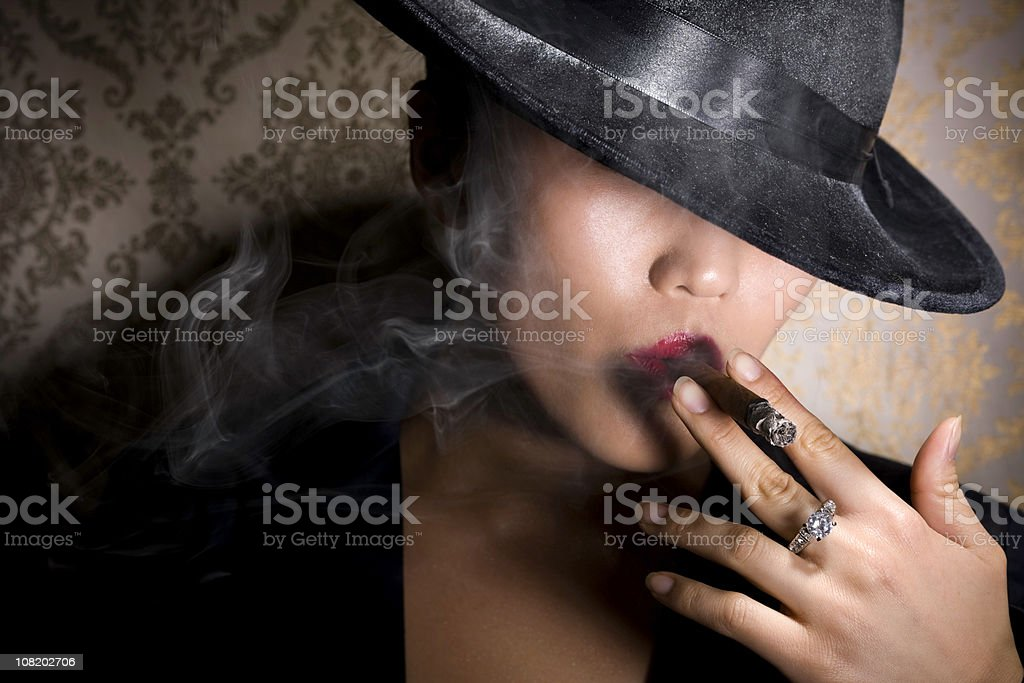 Asian Gangster Woman in Fedora Smoking Cigar with Diamond Ring stock photo
