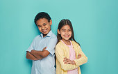 Asian girl and African American boy standing back to back with arms crossed on a turquoise background