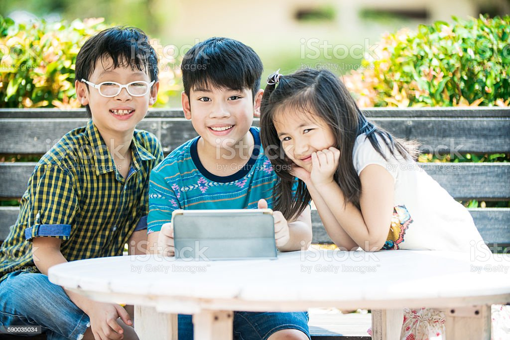 Asian girl and boy sitting and using digital tablet stock photo