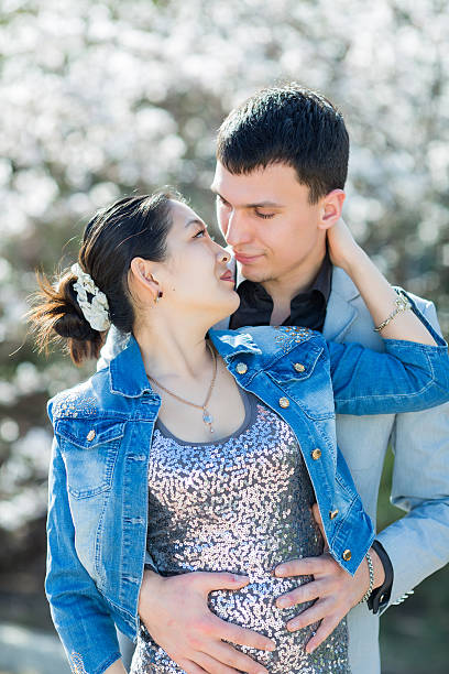 Asian girl and european guy kissing in park stock photo