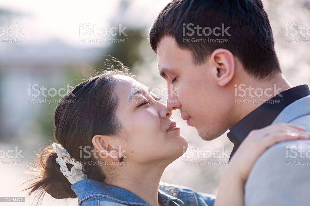 Asian girl and european guy kissing on open air stock photo