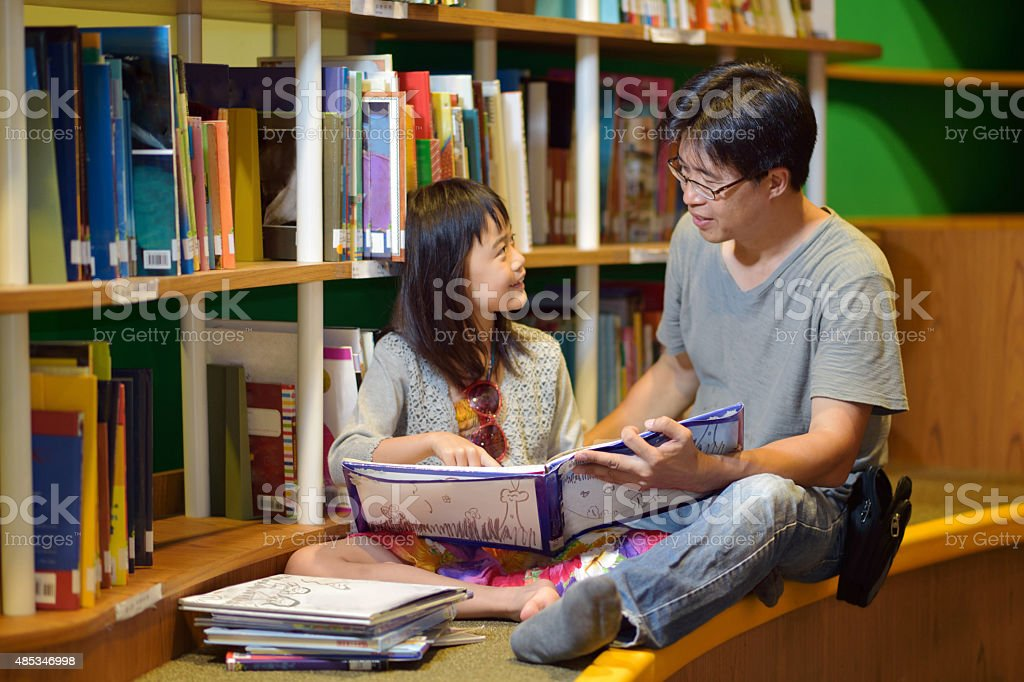 Asian girl and father reading in library stock photo