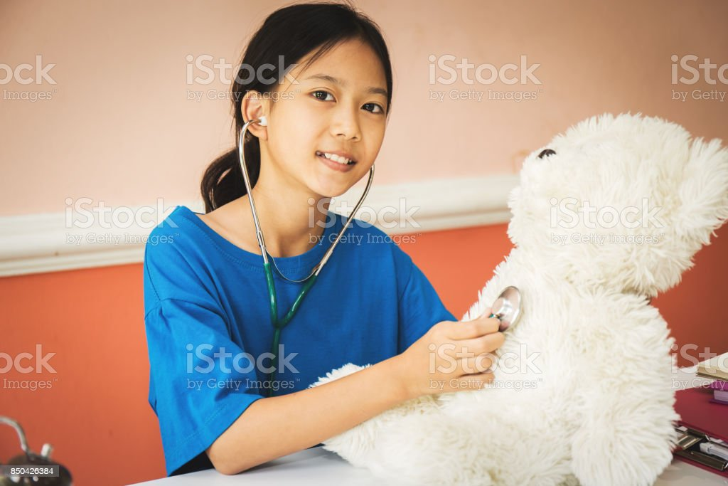 Asian girl being played as a doctor with heart disease to teddy bears. stock photo