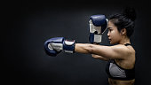 Asian girl boxer punching with blue boxing gloves on black background in studio. Martial arts and female kickboxing concept