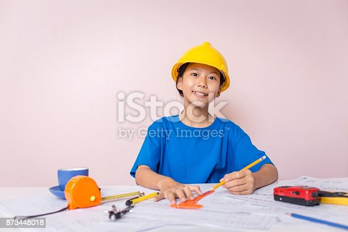 istock Asian girl child playing as an engineer the building layout and helmet are smiling and happy on weekends. 873448018