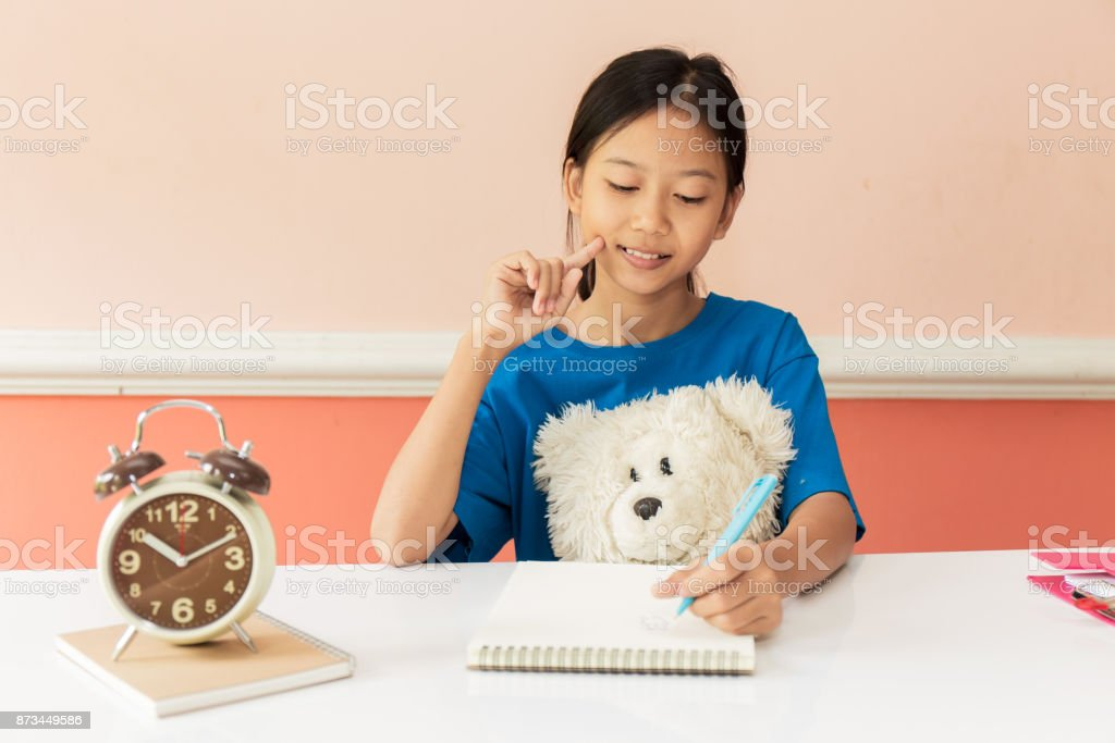 Asian girl child playing as an engineer the building layout and helmet are smiling and happy on weekends. stock photo