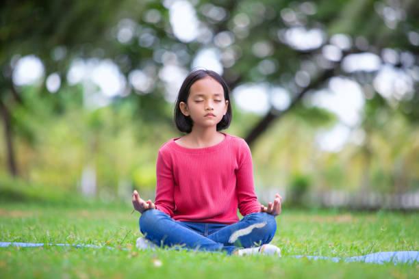 chica asiática haciendo pose de yoga en el parque al aire libre - foto de stock