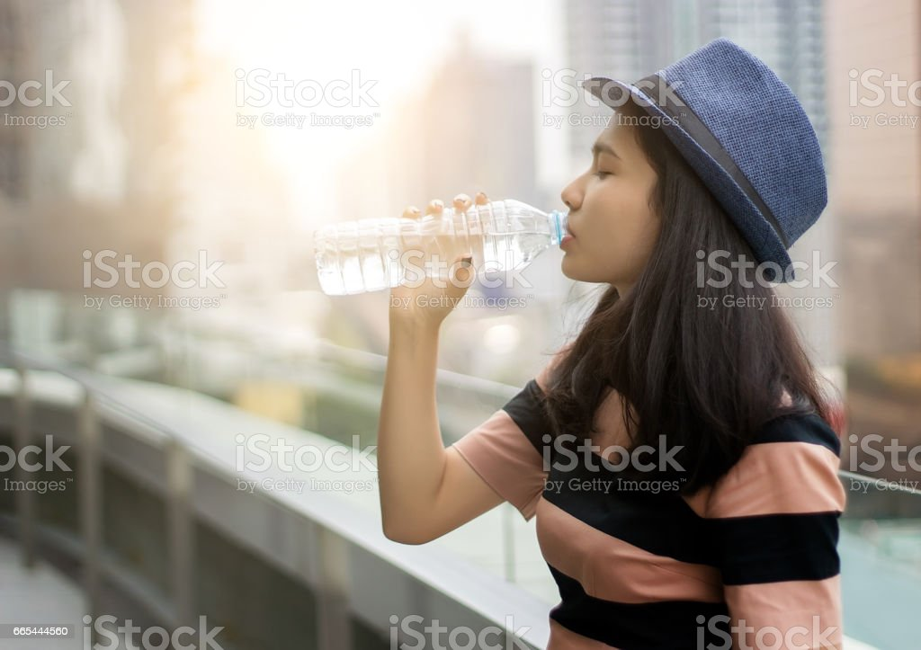 asian girl drinking water outdoor short in summer stock photo