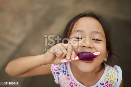 Asian girl eating ice cream in outdoor. Filipina kid eating an ice cream and staring at camera.