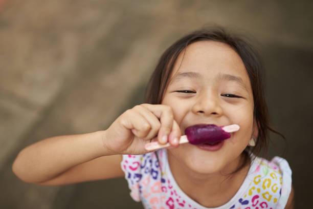 aziatisch meisje eten ijs in de buitenlucht - ijslollie bevroren zoetigheid stockfoto's en -beelden