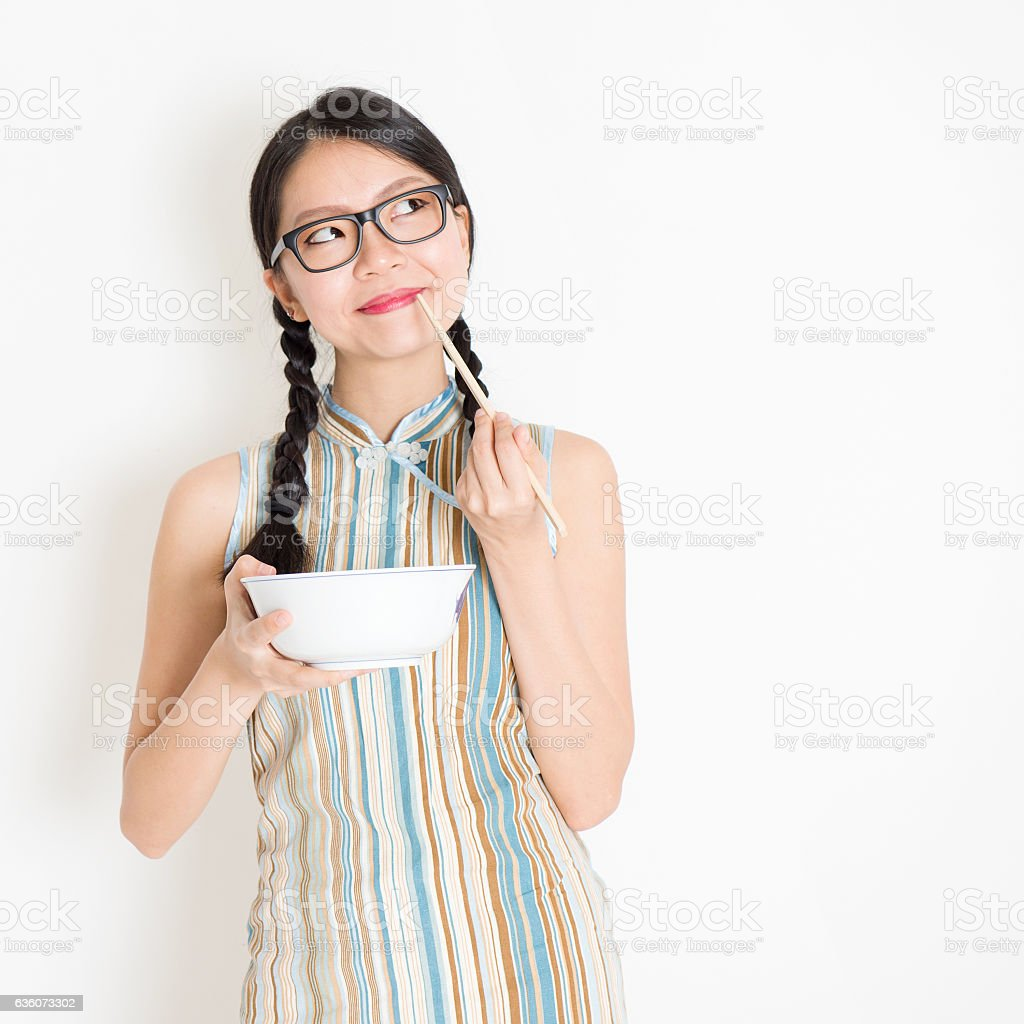 Oriental girl eating with chopsticks and thinking stock photo