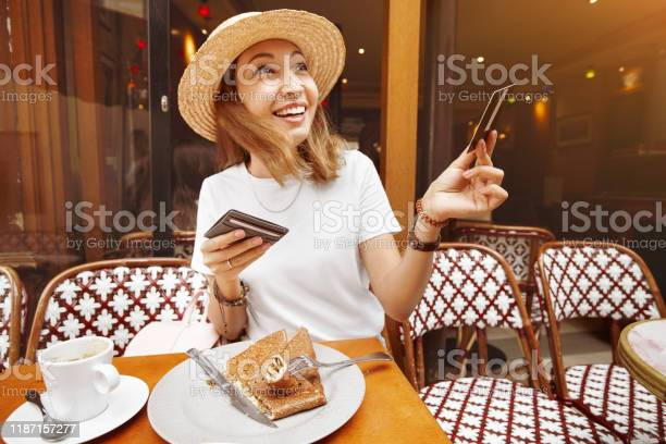 Asian girl finished breakfast in a paris retro cafe and pays for by picture id1187157277?b=1&k=6&m=1187157277&s=612x612&h=edpp1 dgyivykwdmfa5bdo0tywmlin1uh8lr3xnq7f4=