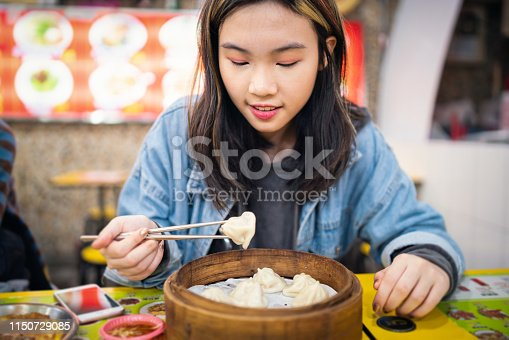 Asian girl having Chinese steamed buns.