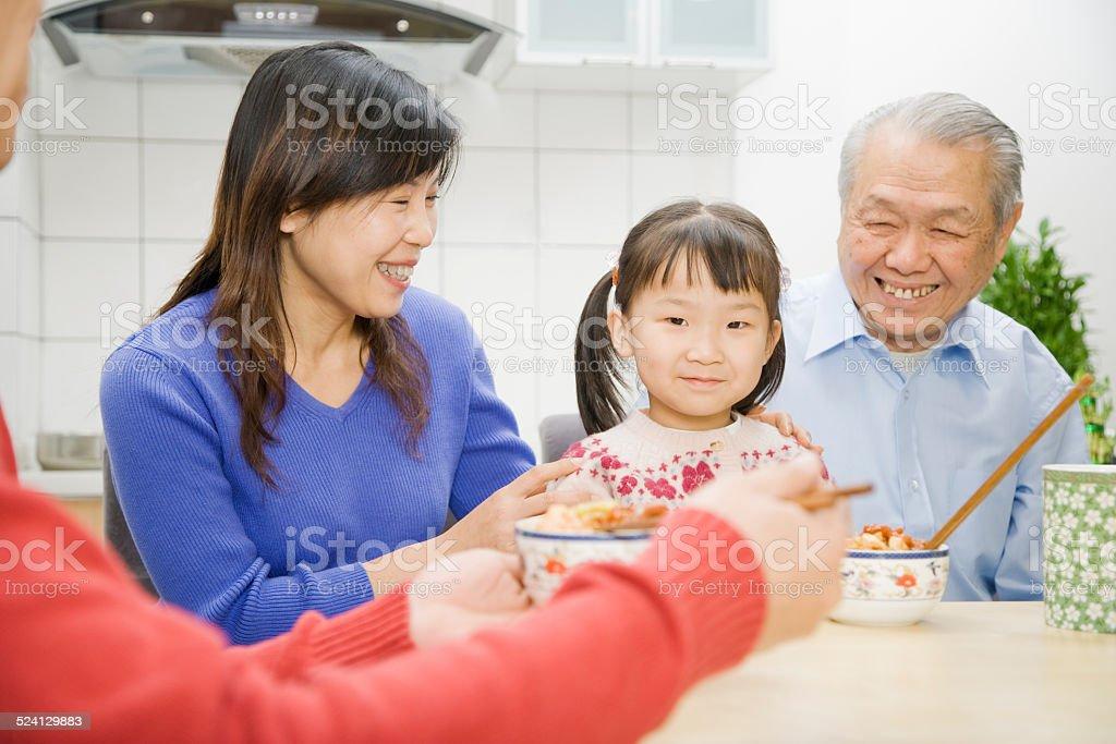 Asian girl having dinner with family stock photo