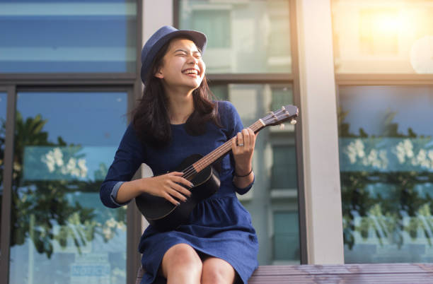 asiatische mädchen spaß mit ukulele - ukulele songs stock-fotos und bilder