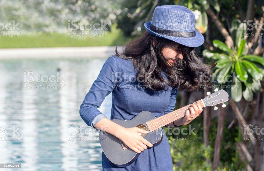 asian girl having fun with ukulele stock photo