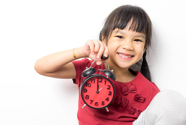 Asian girl holding alarm clock that count lunch time. Asian girl is holding an alarm clock that count for lunch time. Little Asian girl is very happy to get a lunch break. Asian girl is smiling and holding an alarm clock counting down to 12. clock hand stock pictures, royalty-free photos & images