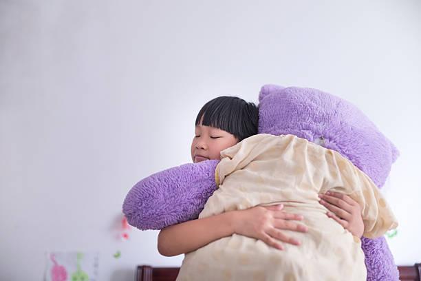 asiatische mädchen umarmen ihr bär spielzeug - lila mädchen zimmer stock-fotos und bilder